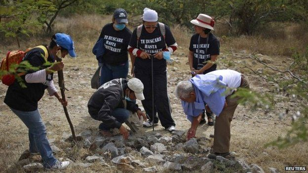People with missing relatives search an area containing mass graves in La Joya, on the outskirts of Iguala, Guerrero state, on 29 November 2014.