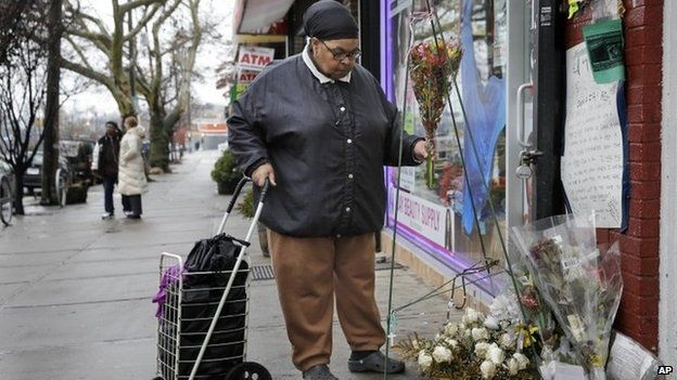 A woman, who did not want to give her name, places flowers at a memorial for Eric Garner near the site of his death in the borough of Staten Island Wednesday, Dec. 3, 2014., in New York