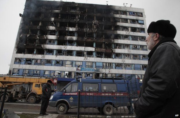 A man looks up at the burnt publishing house in Grozny, 4 December