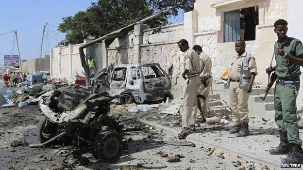 """Somali security stand at the scene of an explosion in front of the airport in Somalia""""s capital Mogadishu, 3 December 2014"""