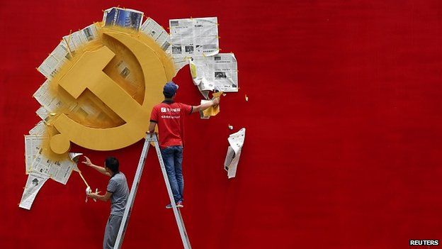 Workers repaint hammer and sickle symbol of Chinese Communist Party flag at Nanhu Revolutionary Memorial museum in Jiaxing, Zhejiang province. May 2014