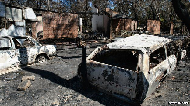 Burnt out cars sits in front of a destroyed house at Mount Victoria in the Blue Mountains. 21 Oct 2013