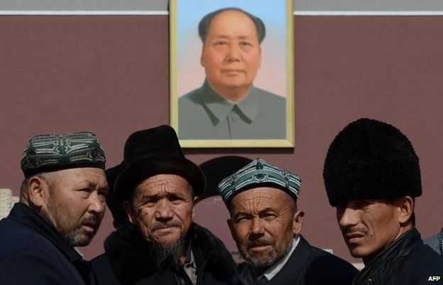Uighurs pose in front of a portait of Mao at Tiananmen Square in Beijing, China