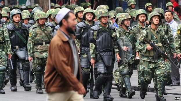 Armed Chinese soldiers march on patrol as a Uighur man crosses the street in Urumqi on 15 July, 2009 in northwest China's Xinjiang province