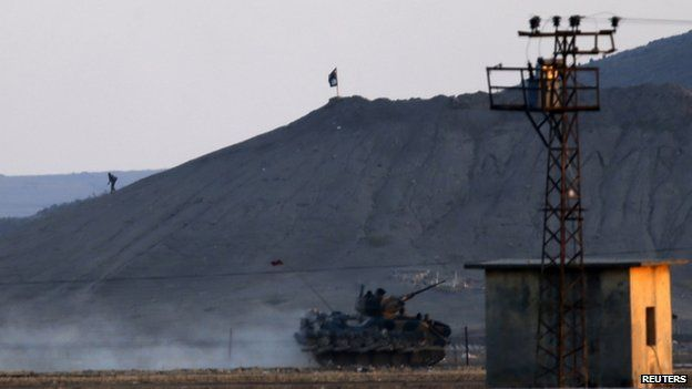 An Islamic State fighter walks near the group's black flag on a hill near the besieged Syrian town of Kobane as a Turkish military vehicle passes just across the border, 7 October