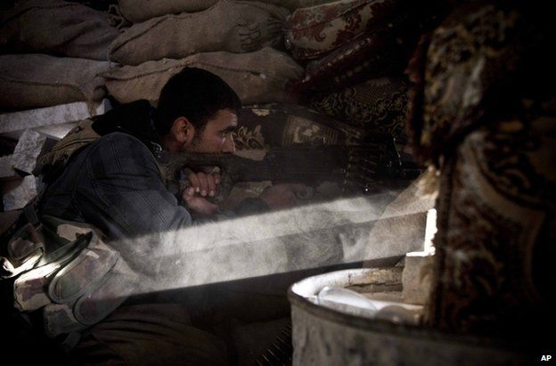 A Kurdish fighter fires on an Islamic State position at Kobane, 23 November