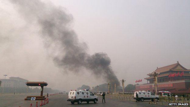 Police cars block off the roads leading into Tiananmen Square as smoke rises into the air after a vehicle crashed in front of Tiananmen Gate in Beijing on 28 October, 2013