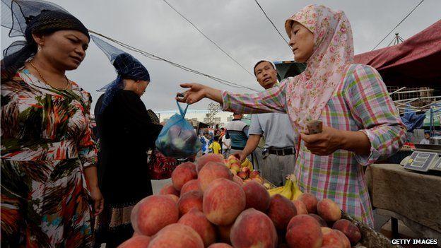 This photo taken on 27 June, 2013 shows Uighur traders at the main bazaar in Turpan, Xinjiang region