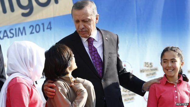 Turkey's President Tayyip Erdogan talks with during a school opening ceremony in Ankara