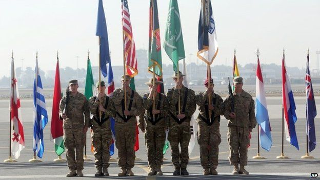 International Security Assistance Forces take party in a ceremony in Kabul, Afghanistan, Monday, Dec. 8, 2014.