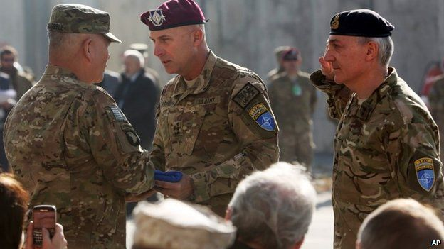 International Security Assistance Force Joint Command (IJC), Lieutenant General Joseph Anderson, center, hands over the flag of the IJC to commander of International Security Assistance Force, General John F. Campbell, left, a ceremony in Kabul, Afghanistan, Monday, Dec. 8, 2014.