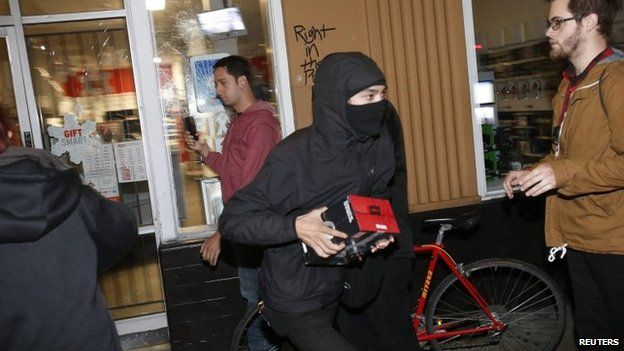 A man carries goods from a vandalised store in Berkeley, California