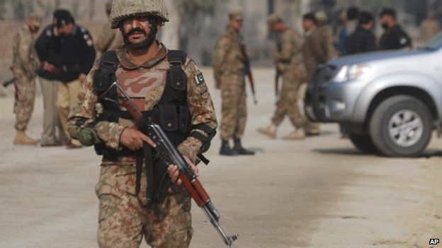 Pakistani army soldiers cordon off the area of a bombing in Peshawar, Pakistan , Nov. 21