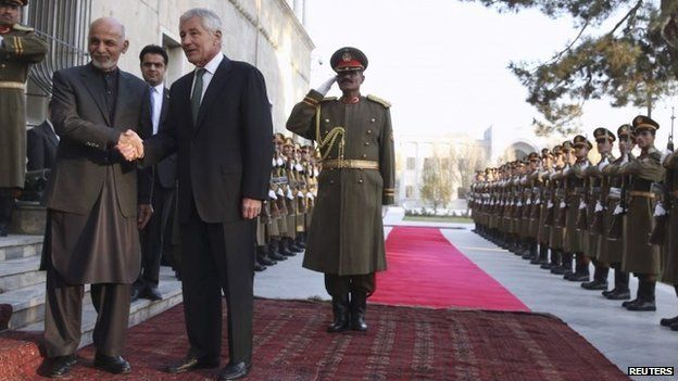 Afghanistan's President Ashraf Ghani shakes hands with US Secretary of Defense Chuck Hagel during an arrival ceremony at the Presidential Palace in Kabul December 6