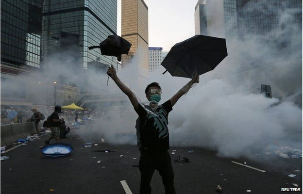 A protester (C) raises his umbrellas in front of tear gas which was fired by riot police to disperse protesters blocking the main street to the financial Central district outside the government headquarters in Hong Kong, 28 September 2014.