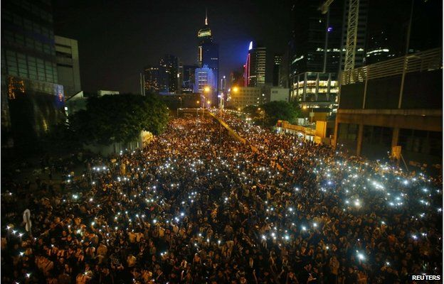 Protesters hold their mobile phones as they block the main street to the financial Central district, outside the government headquarters, in Hong Kong 29 September 2014