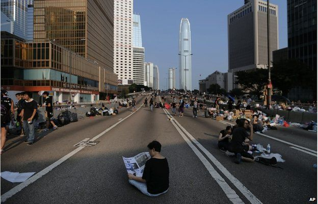 A woman sits and reads the newspaper in the middle of a street which pro-democracy activists have made camp at, Tuesday, 30 Sept 2014 in Hong Kong.