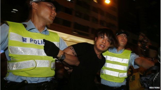 An anti-Occupy Central protester is detained by policemen after he broke through a cordon line, trying to charge pro-democracy protesters, at Hong Kong's shopping Mong Kok district, where a main road is occupied, 3 October 2014.