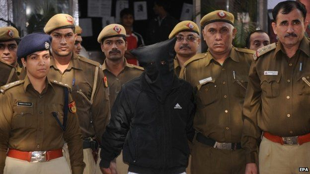 Police personnel escort taxi driver (wearing mask), accused of raping a female finance company executive, as he is taken to court in New Delhi, 08 December 2014.