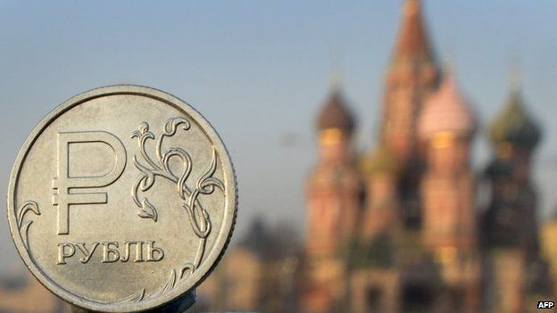 A Russian rouble coin is pictured in front of St. Basil cathedral in central Moscow,