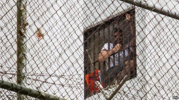 Leopoldo Lopez appears in a window of his cell on 15 November 2014.