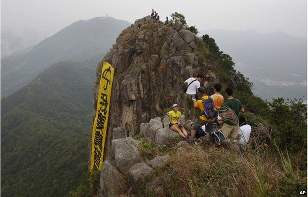 "Hikers take pictures of the yellow banner with the words reading: ""I want genuine universal suffrage"" in Chinese and ""Umbrella Movement"" in English hanging from the face of Lion Rock mountain in Hong Kong Thursday, 23 October 2014"