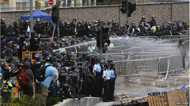 Riot police use a water cannon to disperse protesters during clashes outside the government headquarters in Hong Kong 1 December 2014
