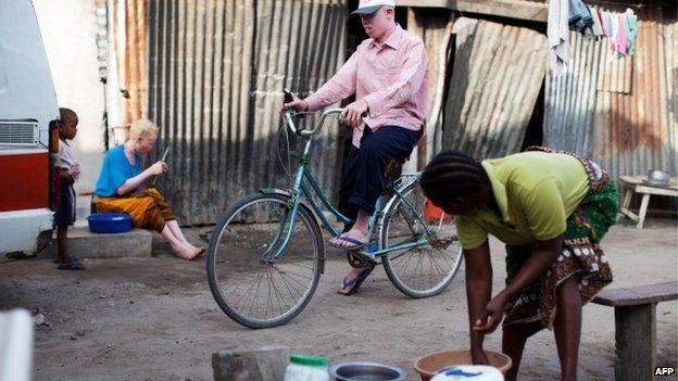 Fikiri Sultan (C), a member of Tanzania's Albino United football club, rides his bicycle in front of his home in Dar es Salaam on 3 November 2010