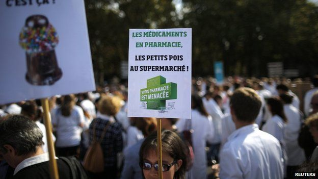 "A pharmacist holds a placard reading ""Drugs in pharmacies, peas at the supermarket. Your pharmacy is threatened"" in a 30 Sept 2014 protest in Nantes"