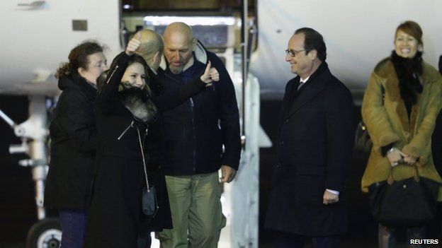 Former hostage Serge Lazarevic is greeted by his daughter Diane (second left), French President Francois Hollande (second right) and Defence Minister Jean-Yves Le Drian at his arrival at the Villacoublay military airport, near Paris, 10 December 2014.