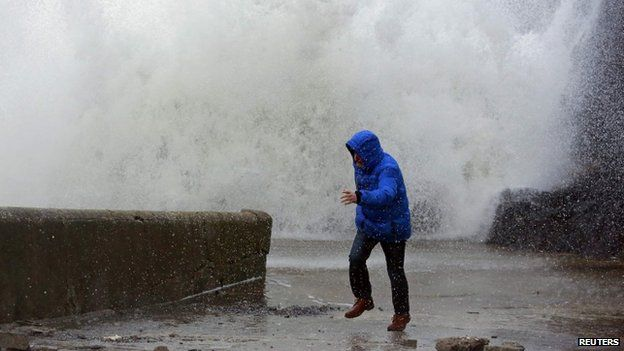 A man runs as a huge wave breaks on a sea wall nearby