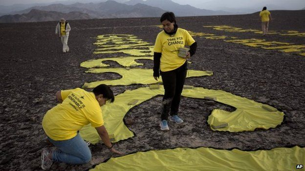 """Greenpeace activists arrange the letters delivering the message """"Time for Change: The Future is Renewable"""" next to the hummingbird geoglyph in Nazca on 8 December, 2014."""