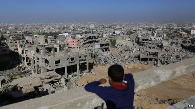 Palestinian boy looks at rubble of houses