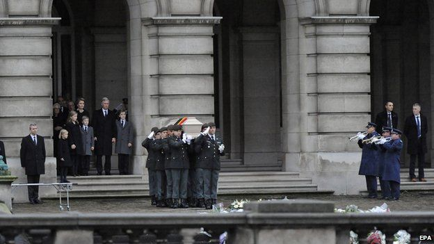 Pallbearers carry the coffin of Queen Fabiola outside the Brussels Palace
