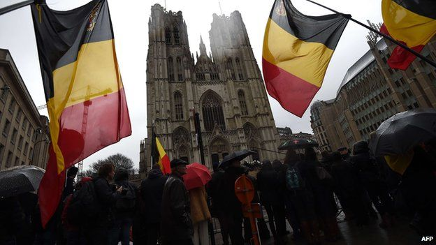 Onlookers wave Belgium flags as the coffin arrives at the Saint Michael and Saint Gudula Cathedral in Brussels