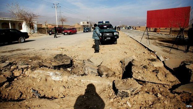 Afghan security officials stand near the site of an attack on a US convoy near Bagram air base in Afghanistan - 13 December 2014
