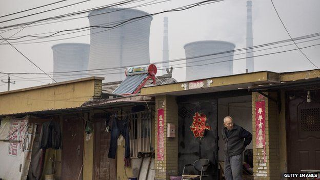 A Chinese man stands in front of his home as a coal fired power plant is seen in the background on November 19, 2014 in Beijing,