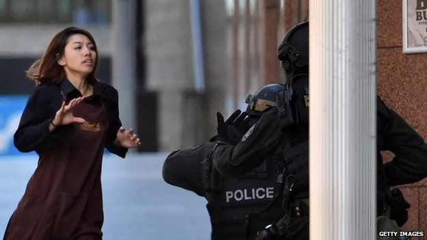 A former hostage wearing a Lindt uniform runs towards police from a cafe in central Sydney where a gunman is holding people captive