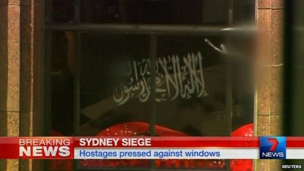 Black flag bearing the shahada held up to a window of the Lindt Cafe in Sydney, Australia, on 15 December 2014