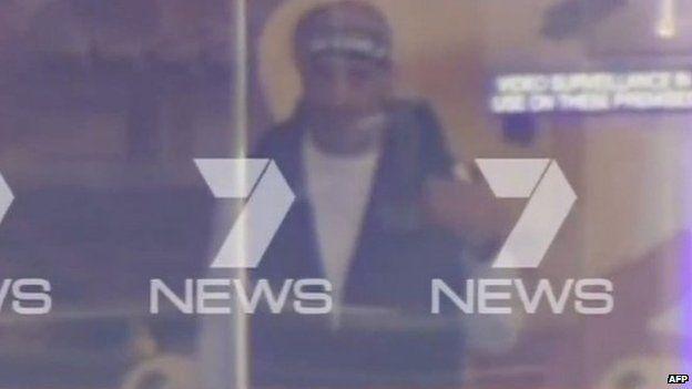 Man wearing a bandana seen through window of Sydney cafe