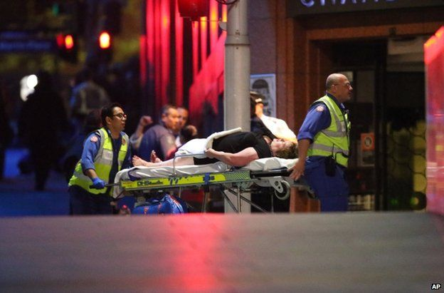 An injured man is wheeled to an ambulance in Sydney, 15 December