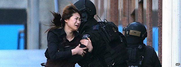 An escaping hostage is caught by a policeman in Sydney, 15 December