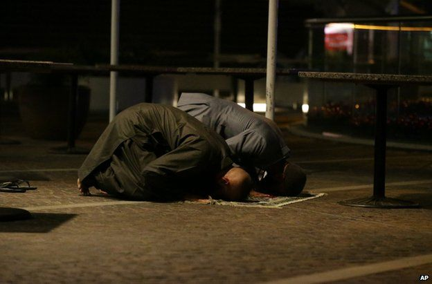 Two Muslims pray for peace in the central business district of Sydney, 16 December