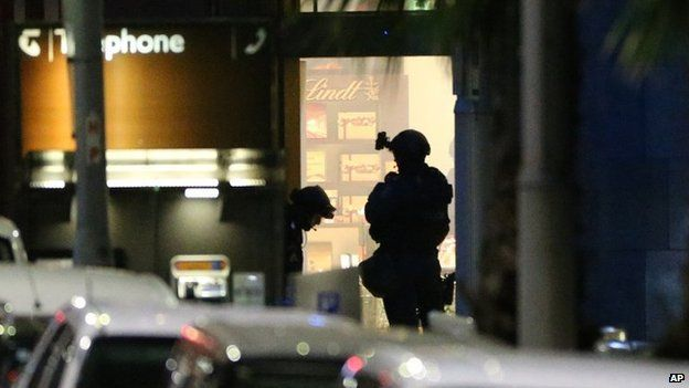 Armed tactical response officers stand ready to enter the Lindt cafe during a siege in Sydney on 16 December 2014