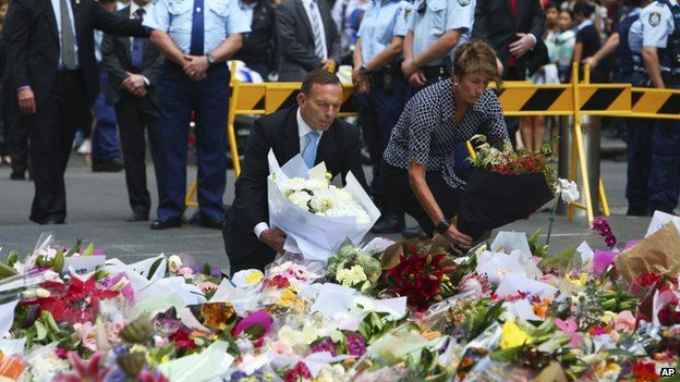 Australian Prime Minister Tony Abbott and his wife Margie pay their respect to the victims of the siege in Martin Place in Sydney central business district, Australia. Tuesday, 16 December 2014