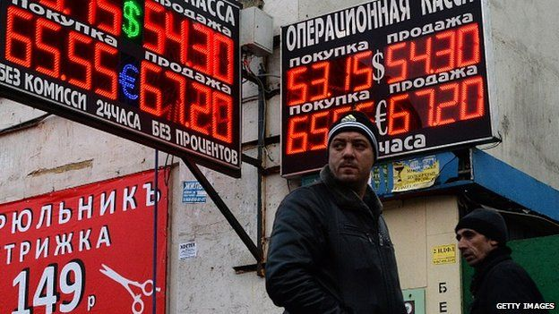 Pedestrians walk past a board listing foreign currency rates against the Russian rouble outside an exchange office in Moscow on December 3, 2014