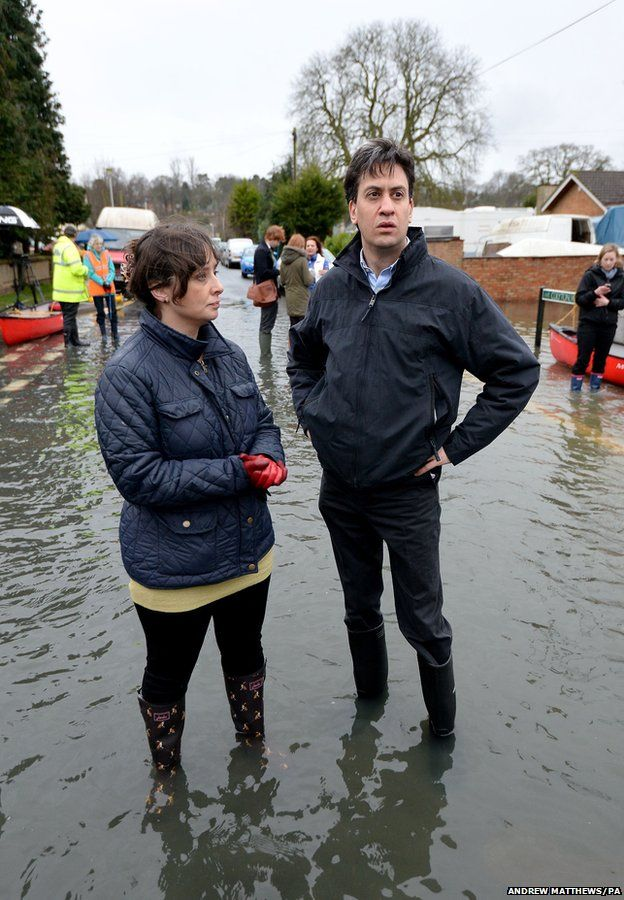 Labour leader Ed Miliband (right) and Victoria Groulef (left), Labour's Parliamentary Candidate for Reading West, during a visit to the flooding in Purley on Thames in Berkshire