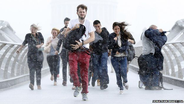 Pedestrians dash through torrential rain along the Millennium Bridge, Southwark, London, as the remnants of Hurricane Bertha swept across parts of the country