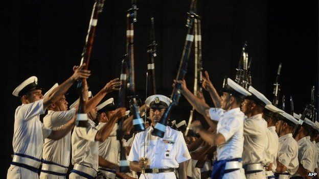 Indian navy sailors throw their rifles towards each other as an officer walks past during a rehearsal for Navy Day celebrations in front of The Gateway of India in Mumbai on 2 December 2013