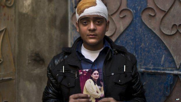Baqir Jafri, a survivor of the Peshawar school massacre, holds a photo of his mother